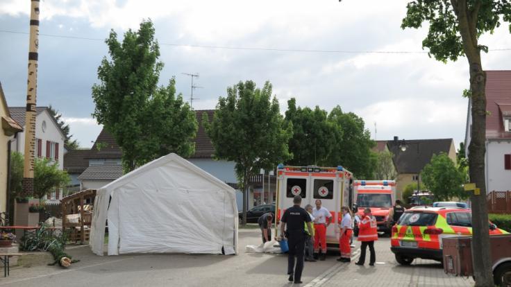 Rettungskräfte und Polizei sind neben einem Maibaum im Einsatz, dessen Spitze zuvor abgebrochen und abgestürtzt war. (Foto)