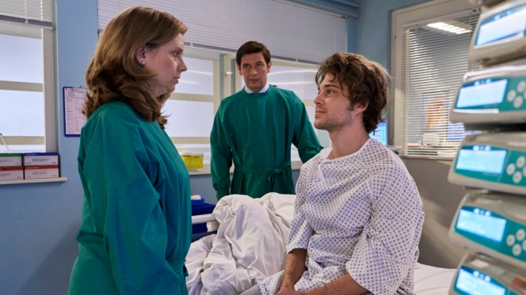 Kris Haas (Jascha Rust, rechts) wünscht sich in den schweren Stunden vor seiner OP von seinem Vater Simon (Tom Mikulla, mi.) und seiner Mutter Sylvia (Nina Weniger, li.) Unterstützung.