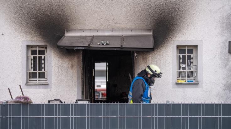 Ein Feuerwehrmann mit Atemschutzausrüstung verlässt nach einem Brand ein Haus. Bei dem Brand in dem Nürnberger Wohnhaus sind vier Kinder und eine Frau ums Leben gekommen. (Foto)