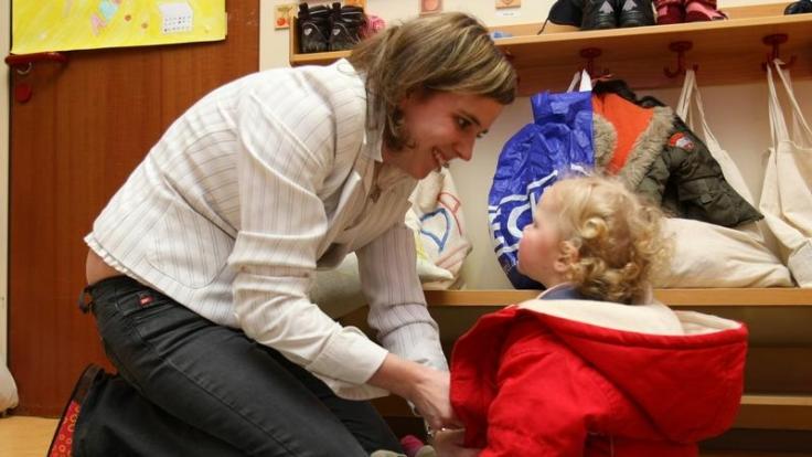 Eine Jacke anzuziehen, ist ganz schön schwierig: Kinder sollten es immer wieder selbst probieren, bevor Erwachsene helfen. (Foto)