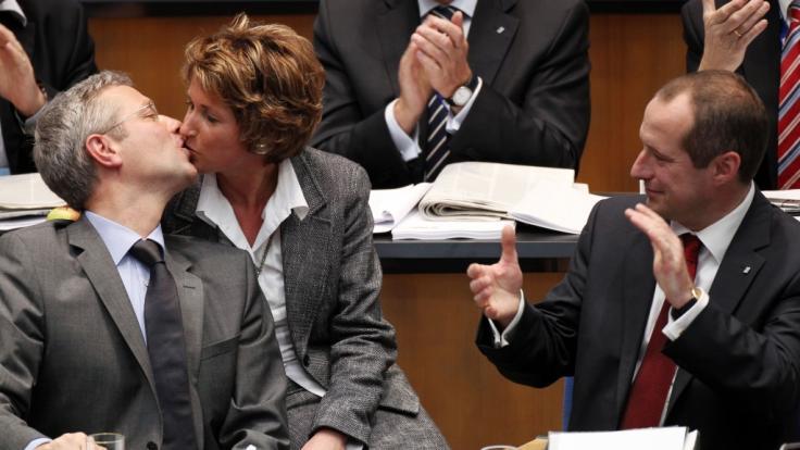 Der CDU-Landesvorsitzende Norbert Röttgen gab 2010 in Bonn nach der Bekanntgabe des Wahlergebnisses seiner Frau Ebba einen Kuss, während der designierte Generalsekretär Oliver Wittke (r) applaudierte.