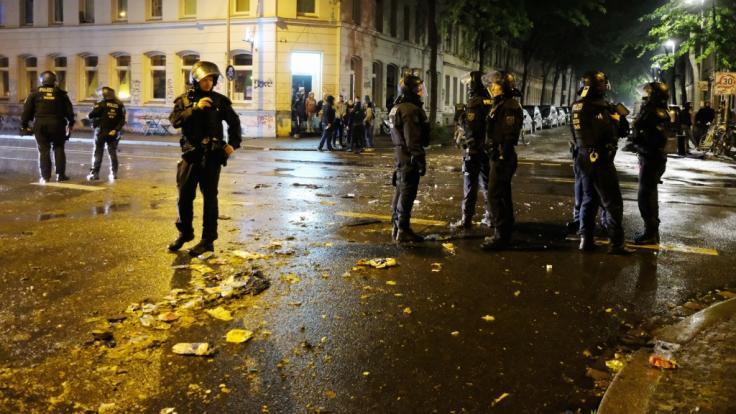 Polizisten sichern eine Straße im Osten der Stadt, im Hintergrund sind die Reste einer Barrikade zu sehen. (Foto)