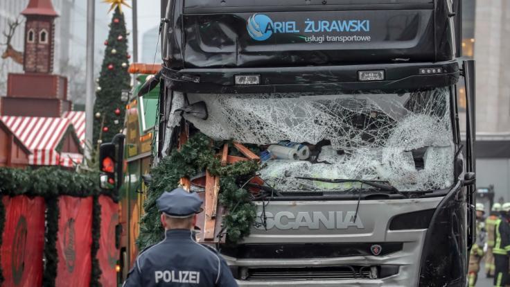 Ein Polizist steht vor dem Tatfahrzeug, einem polnischer Lastwagen, am Weihnachtsmarkt am Breitscheidplatz nachdem der Attentäter Anis Amri mit dem Fahrzeug über den Platz gerast war.