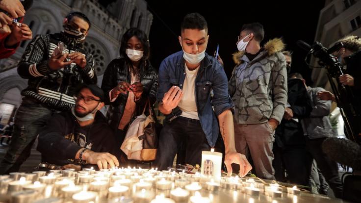 Menschen zünden Kerzen auf der Straße vor der Kirche Notre Dame für die Opfer einer Messerattacke an. (Foto)