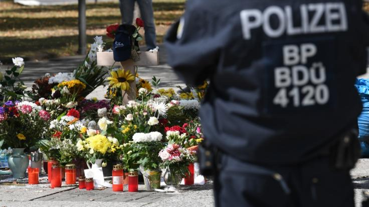 Bei einer Gedenkveranstaltung am Tatort in Chemnitz steht ein Polizist neben den Blumen.