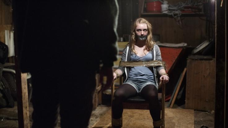 Lykke (Sara Månberg) ist mit Klebeband an einen Stuhl gefesselt und schaut einen Mann an, der ihr gegenüber sitzt. Ihr Mund ist ebenfalls mit Klebeband beklebt. (Foto)