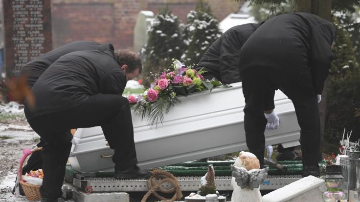 Bestatter senken den Sarg des sechsjährigen Mädchens, das am 12.01.2019 in Torgelow getötet wurde, auf dem Friedhof ins Grab ab.