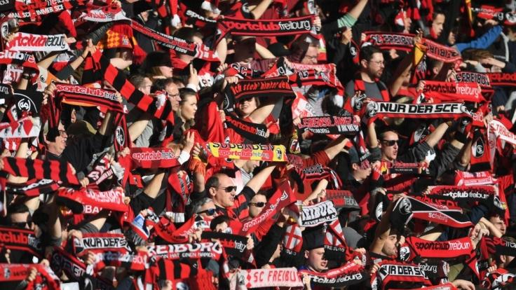Mit ihren Schals in der Luft unterstützen die Fans vom SC Freiburg ihr Team. (Symbolbild)