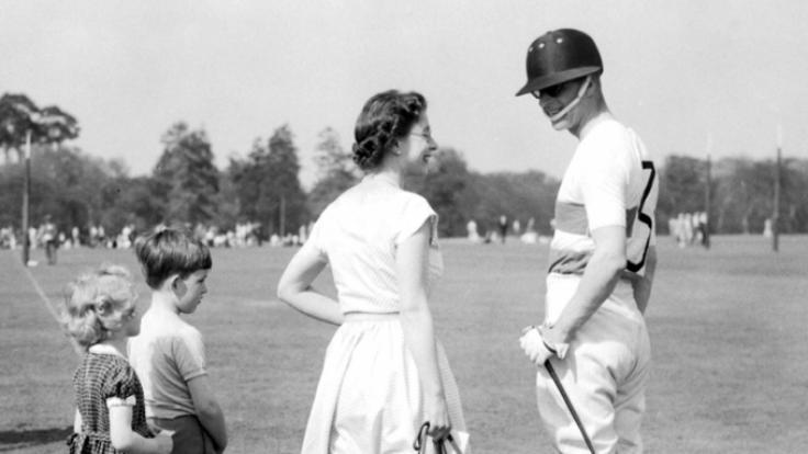Königin Elizabeth II. hält am 06.05.1956 in Windsor (Großbritannien) ihren Corgi-Hund an der Leine und unterhält sich mit ihrem Mann Prinz Philip. (Foto)