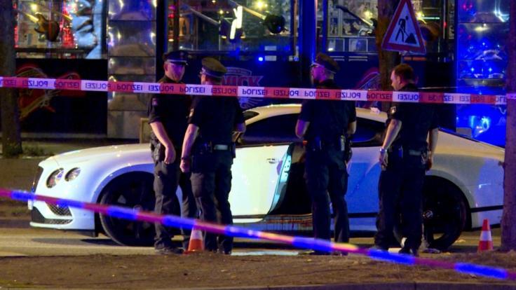Polizisten stehen neben dem Auto auf dem Hamburger Millerntorplatz, nachdem Schüsse auf den Fahrer abgegeben wurden.