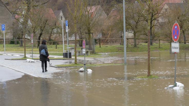 Eine Frau geht an einem überfluteten Parkplatz vorbei.