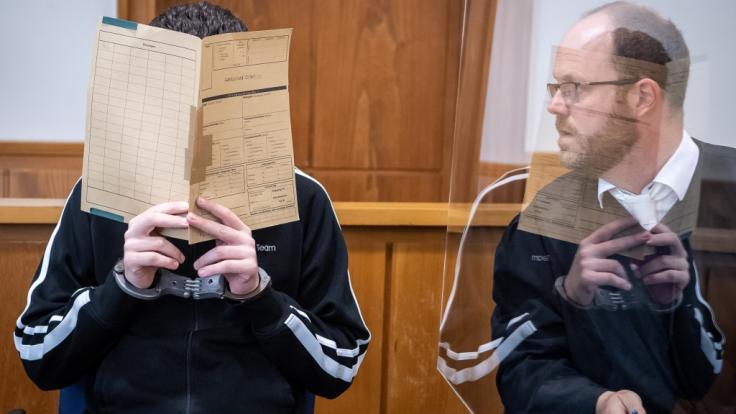 Der 21-jährige Angeklagte spricht vor Prozessbeginn mit seinem Anwalt Guido Diekhaus (r). (Foto)