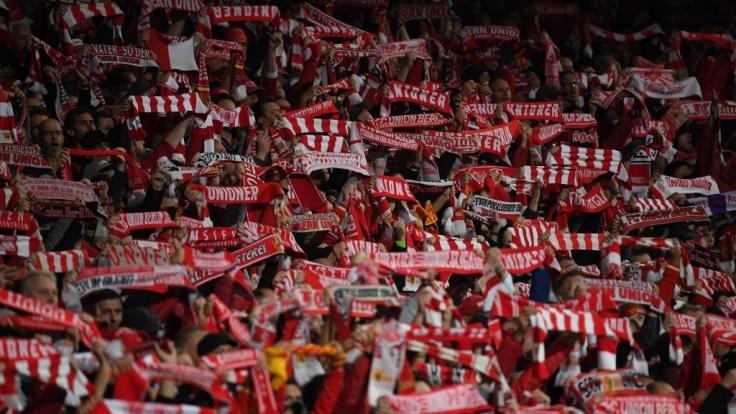 Mit erhobenen Schals feuern die Fans des 1. FC Union Berlin ihren Verein an. (Symbolbild)