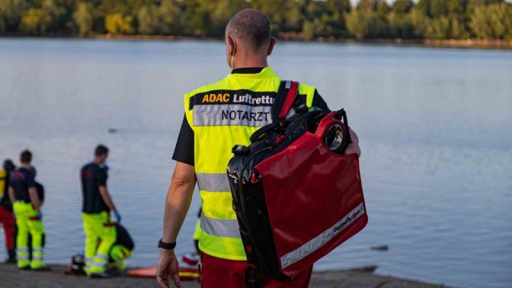 Einsatzkräfte stehen am Rather See und helfen bei der Bergung eines 13-jährigen Mädchens. Das Mädchen war am Mittwochabend mit einer Freundin in dem See geschwommen und plötzlich verschwunden. (Foto)