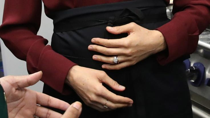 Schützend hält Meghan Markle die Hände vor ihren Babybauch.