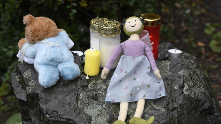 Eine Puppe und Kerzen liegen auf einem Felsen vor dem Haus in Solingen, in dem die junge Mutter ihre fünf Kinder getötet haben soll. (Foto)