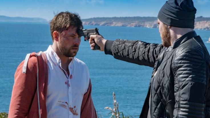 John (Felix von Jascheroff) wird von Erik (Patrick Heinrich) mit einer Waffe bedroht. (Foto)
