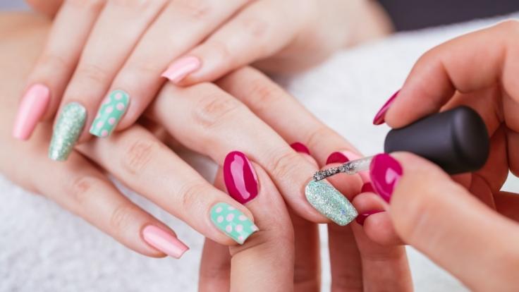 Bunt manikürte Fingernägel sind ein Trend - doch auch gesundheitsschädlich.