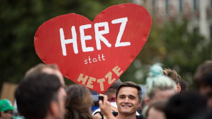 """Ein Teilnehmer der Kundgebung des Bündnisses Chemnitz Nazifrei unter dem Motto """"Herz statt Hetze"""" hält ein Schild in Form eines Herzen hoch. (Foto)"""