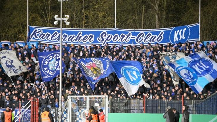 Die Fans vom Karlsruher SC schwenken Fahnen für ihren Verein. (Symbolbild)