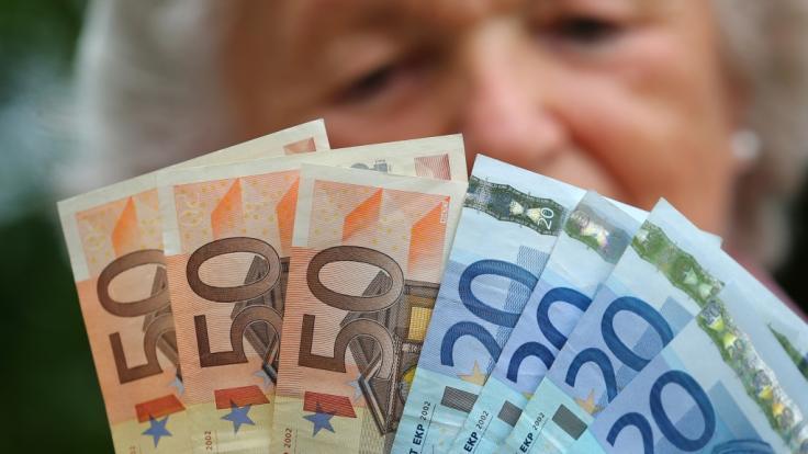 Eine Rentnerin hält verschiedene Euroscheine in ihren Händen. (Foto)