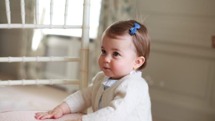 Neugierig und mit süßer Schleife im Haar spielt Prinzesschen Charlotte mit der Kamera.