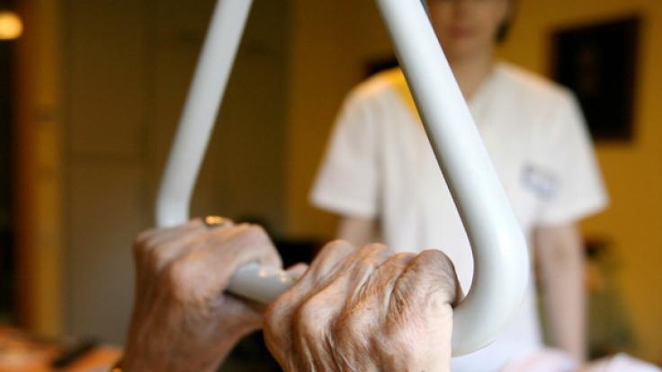 Eine Rentnerin hält sich an dem Handgriff an ihrem Bett fest. (Foto)