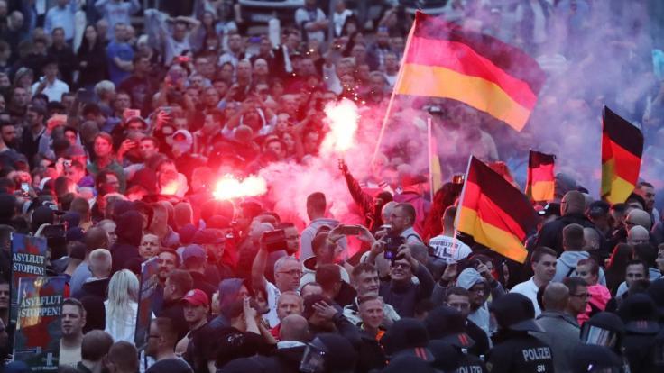 Demonstranten der rechten Szene zünden Pyrotechnik und schwenken Deutschlandfahnen. (Foto)