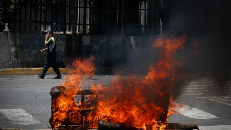 Eine Matratze brennt auf der Straße bei Zusammenstößen zwischen Streitkräfte und Demonstranten, die zur Unterstützung der Opposition um den selbst ernannten Interimspräsidenten Guaido auf die Straße gingen.