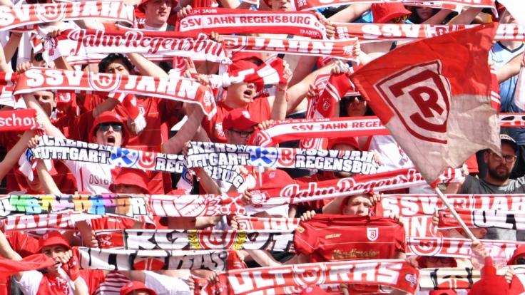 Mit ihren Schals in der Luft feuern die Fans des SSV Jahn Regensburg ihre Mannschaft an. (Symbolbild) (Foto)