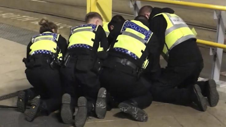 Polizisten halten am Bahnhof Victoria Station einen Mann am Boden, der zuvor drei Menschen mit einem Messer verletzt hatte.