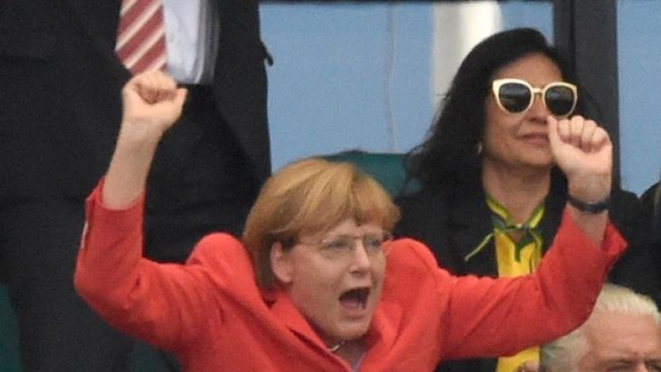 Sonst ist Angela Merkel eher die Freundin subtiler Gesten, doch auf der Fußball-Tribüne lässt sie es richtig krachen.