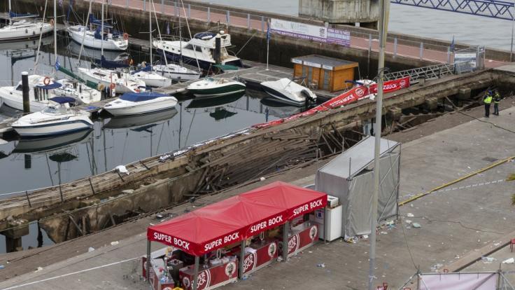 Ein Foto zeigt den zerstörten Holzsteg im spanischen Vigo:Der Steg brach während eines Festivals unter dem Gewicht der Massen zusammen, einige Besucher fielen ins Wasser.