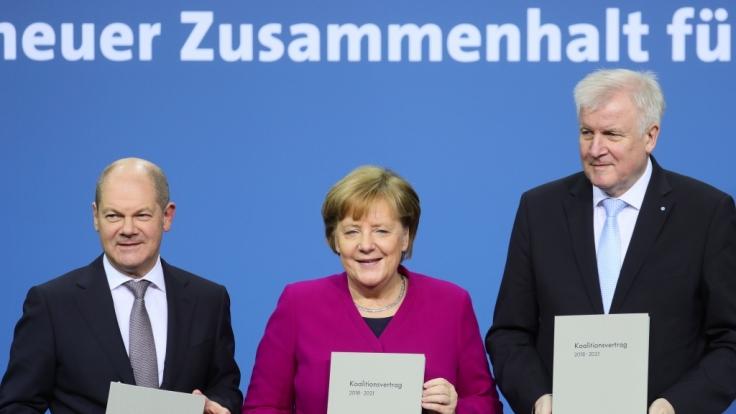 Bundeskanzlerin Angela Merkel (CDU), der CSU-Vorsitzende Horst Seehofer und der kommissarische SPD-Vorsitzende Olaf Scholz zeigen den unterzeichneten den Koalitionsvertrag.