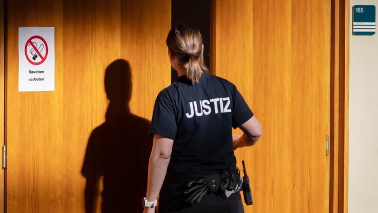 Eine Justizbeamtin öffnet eine Tür des Verhandlungssaals im Landgericht Detmold. (Foto)
