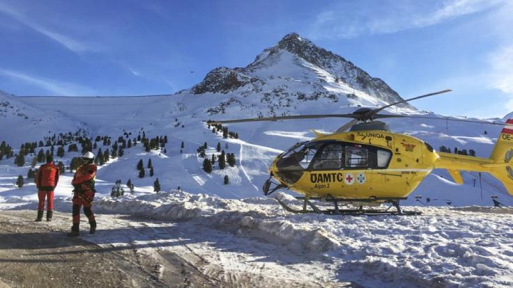 Zwei Rettungshelfer stehen neben einem Helikopter. (Foto)