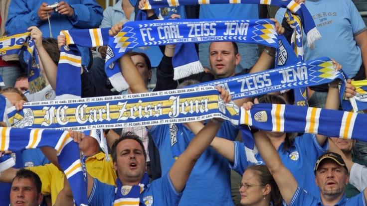 Mit den Schals in der Luft unterstützen die Fans vom FC Carl Zeiss Jena ihren Verein. (Symbolbild)