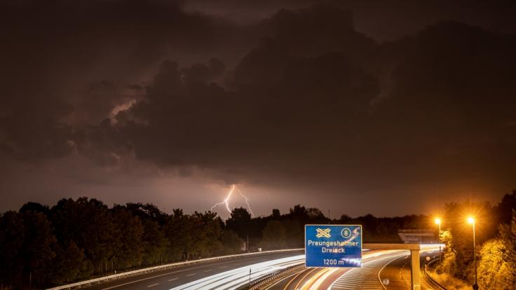 Die zahlreichen Blitze eines fernen Gewitters erhellen die dunklen Wolken über der Autobahn A661 im Nordosten von Frankfurt am Main.
