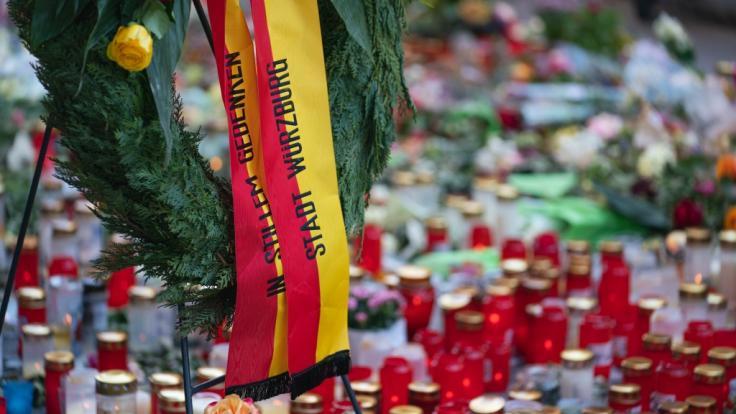 Trauerkerzen und Blumen, sowie ein Kranz der Stadt Würzburg, liegen vor einem Kaufhaus in der Innenstadt, in dem ein Mann Menschen mit einem Messer attackiert hatte. (Foto)