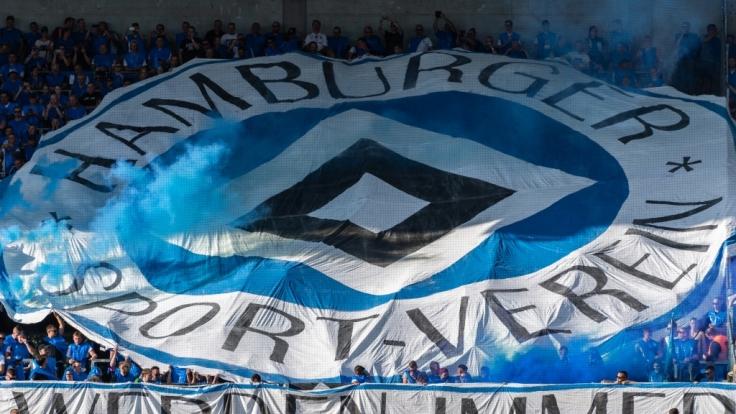 Unter ihrem blauen Wappen feuern die Fans des Hamburger SV ihren Verein an. (Symbolbild) (Foto)