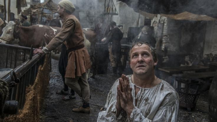 Martin Luther (Maximilian Brückner) kniet auf einer geschäftigen Straße - und betet. (Foto)