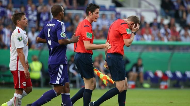 Schiedsrichter Martin Petersen krümmt sich und unterbricht das Spiel, nachdem er von einem Gegenstand am Kopf getroffen wurde.