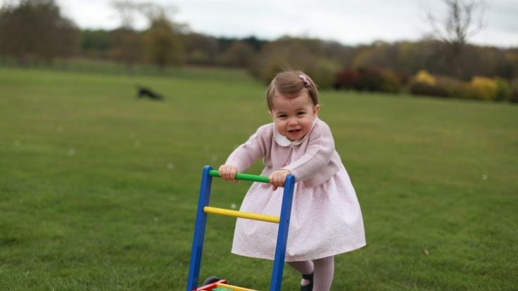 Prinzessin Charlotte beweist im Garten des Kensington Palace, dass sie (mit etwas Hilfe) schon prima laufen kann.