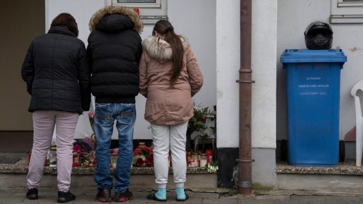Trauernde Nachbarn und Freunde der Familie des Opfers stehen vor dem Haus, in dem die Tochter der Familie von ihrem Freund umgebracht worden war.