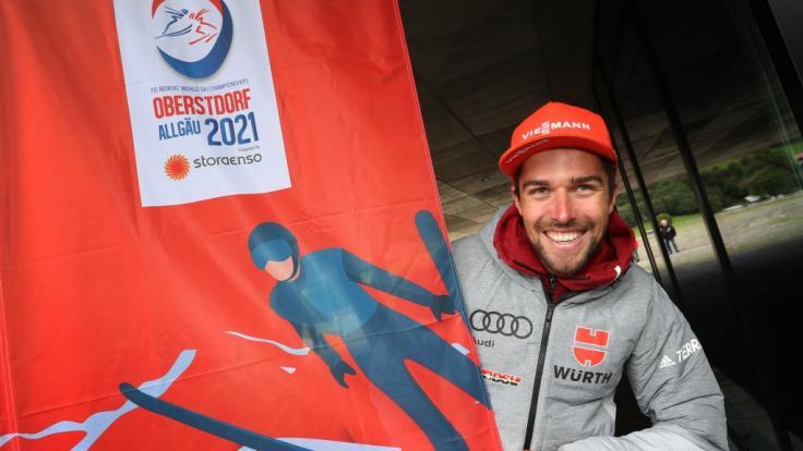 Johannes Rydzek, deutscher Nordischer Kombinierer, steht neben der offiziellen Fahne der Nordischen Ski-WM 2021.