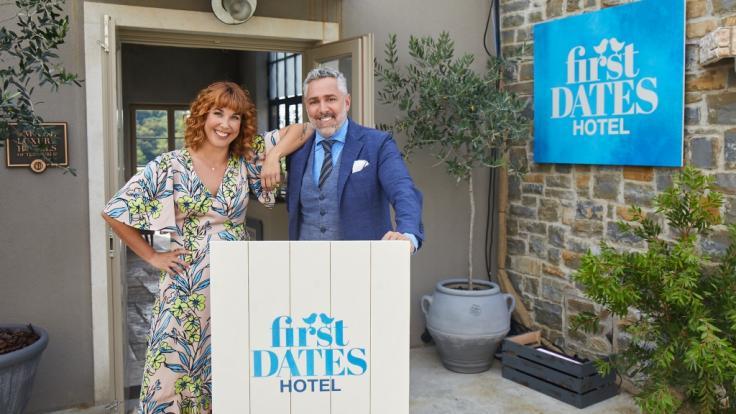 """Rezeptionistin Aline und Gastgeber Roland Trettl begrüßen die Singles im """"First Dates Hotel"""". (Foto)"""
