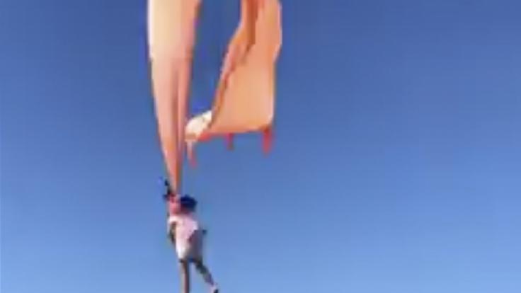 Zahlreiche Menschen werden Zeuge, wie ein Drachen ein 3 Jahre altes Mädchen mit sich in die Höhe zieht. (Foto)