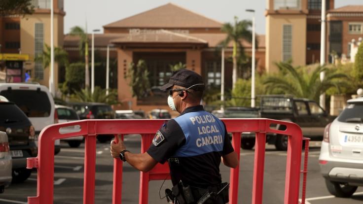 Spanien, Teneriffa: Ein Polizist setzt eine Sperre, die den Zugang zum Hotel H10 Costa Adeje Palace auf Teneriffa blockiert. Nach einem bestätigten Coronavirus-Fall ist das Hotel unter Quarantäne gestellt worden. (Foto)