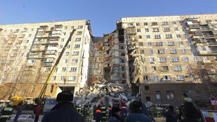 Rettungskräfte stehen vor einem Wohnhaus, das durch eine Gasexplosion beschädigt worden ist.