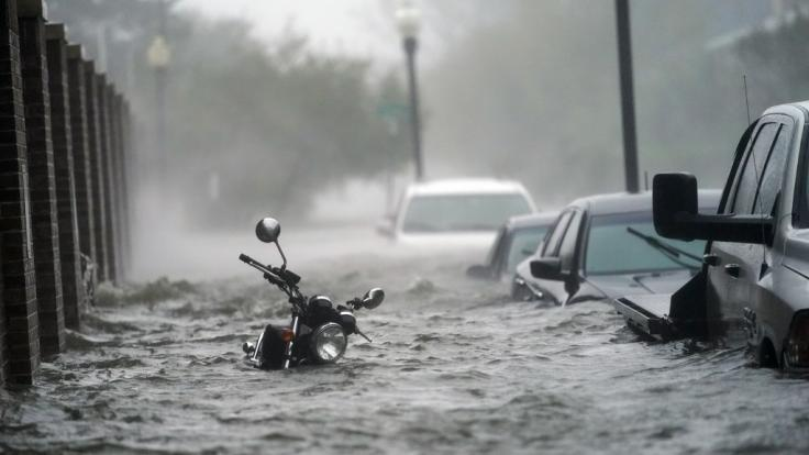 Fahrzeuge stehen auf einer überfluteten Straße. (Foto)
